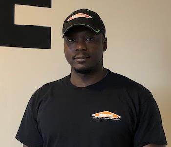 Male employee with SERVPRO hat and shirt standing in front of a white wall.