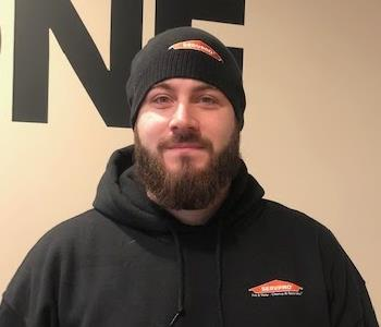 Male employee with dark beard and beenie cap standing