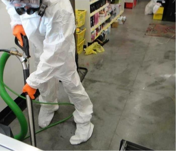 SERVPRO Tech with full protective white suit on vacuuming during a deep clean.