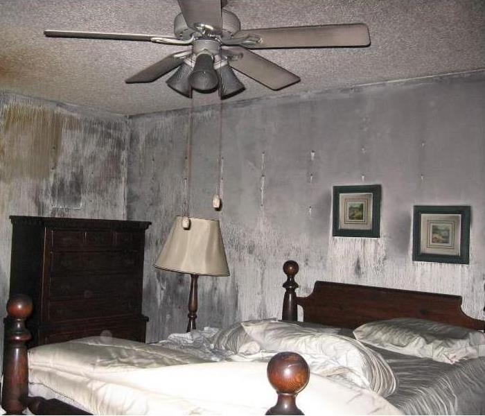 A bedroom where the walls and furniture are grey from smoke damage.