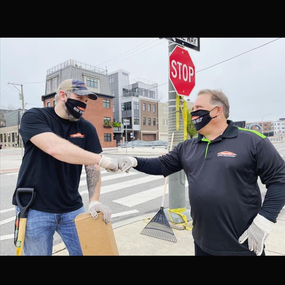 Two male SERVPRO employees bump fists.