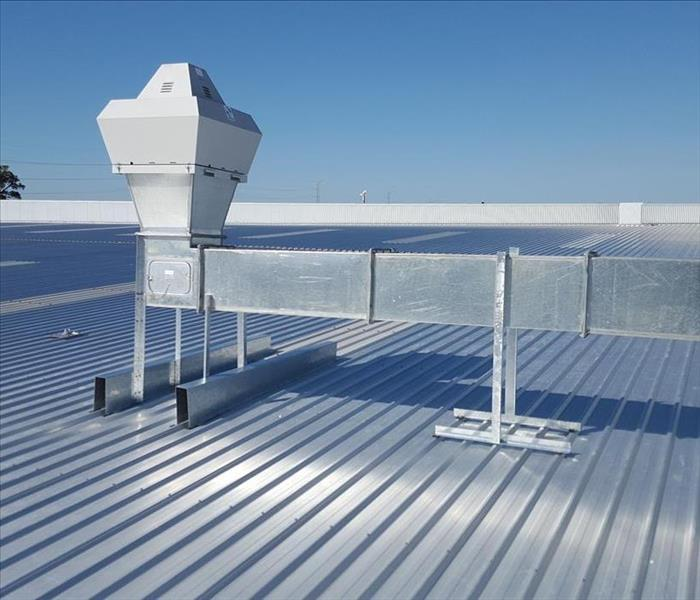 A commercial air condition unit on top of a metal roof.